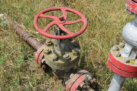 damper: Oil valve with rocking in the background. The gate on an oil well