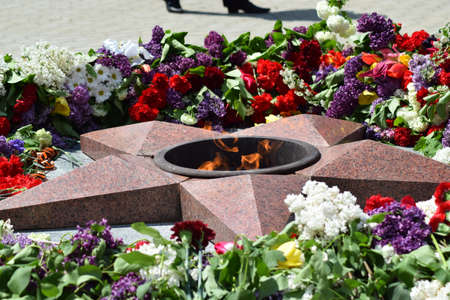 unknown age: The laid flowers to an eternal flame in honor of a Victory Day on May 9. Patriotic traditions.
