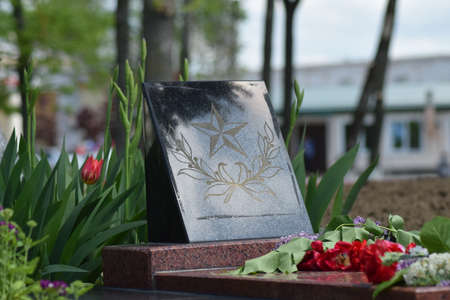 unknown age: The laid flowers to a monument in honor of a Victory Day on May 9. Patriotic traditions. Stock Photo