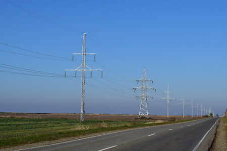 conductivity: Support of electricity cables along the road. Country road. Stock Photo