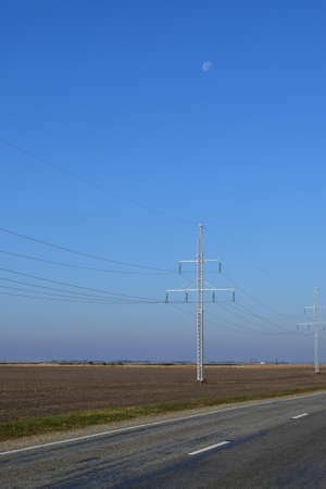voltage gray: Support of electricity cables along the road. Country road. Stock Photo