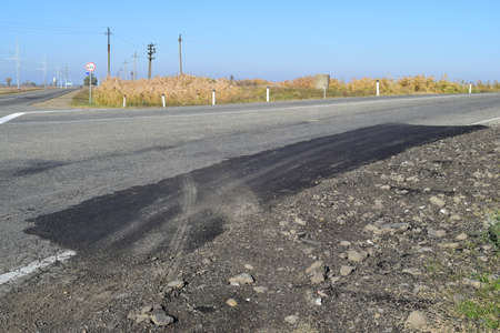 patching: Repair of an asphalt road surfacing. A patch on asphalt.