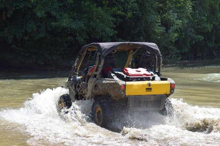 L'homme sur l'ATV traverse un ruisseau. Promenades touristiques sur un terrain de ski de fond. Banque d'images - 48806972