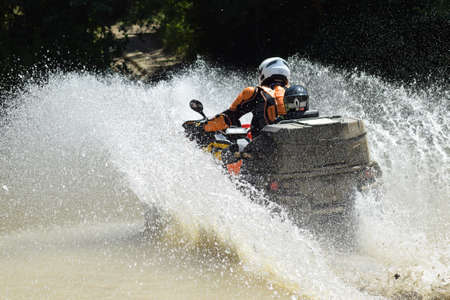 The man on the ATV crosses a stream. Tourist walks on a cross-country terrain.