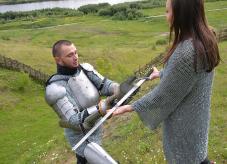 accepts: The knight accepts a sword from hands of the lady. Knightly armor and weapon. Semi - antique photo. Stock Photo