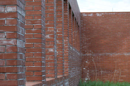 renovate old building facade: Abandoned building of red brick. The walls and windows of the unfinished home.