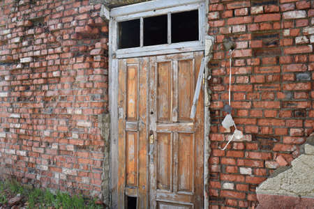 dilapidated wall: Old door on a dilapidated wall. Abandoned building. Stock Photo