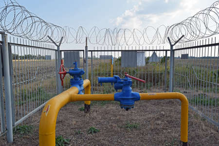 damper: The latch on the underground gas pipeline protected with a fence. Stock Photo