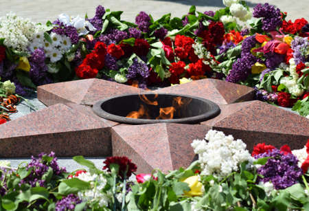 assigned: Eternal flame with flowers assigned to it. Celebration of May 9 Victory in the Great Patriotic War.