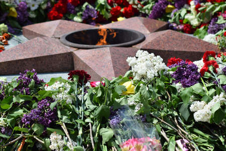 unknown age: Eternal flame with flowers assigned to it. Celebration of May 9 Victory in the Great Patriotic War.