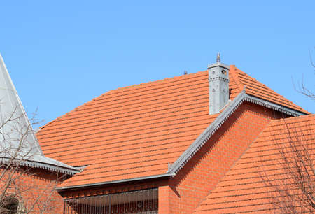 The house with a roof of tiles. The house with gables, windows and tiled roof, equipped with overflow.