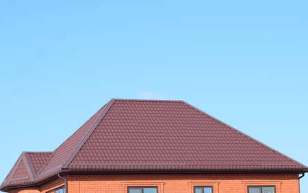 house gables: A house with a roof made of metal sheets. The house with gables, windows and metal roof, equipped with overflow and protection from snow.