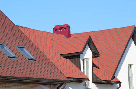 roof profile: A house with a roof made of metal sheets. The house with gables, windows and metal roof, equipped with overflow and protection from snow.