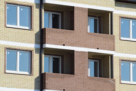 Balconies and windows of a multi-storey new house. New house of brick.