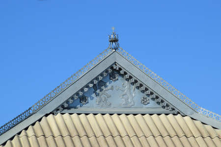 trussing: Decorative elements on the ridge of the roof. The roof of slate and horse of the decorative sheet. Lions and flowers from the sheet metal on the front.