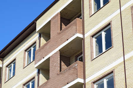 trussing: Balconies and windows of a multi-storey new house. New house of brick.