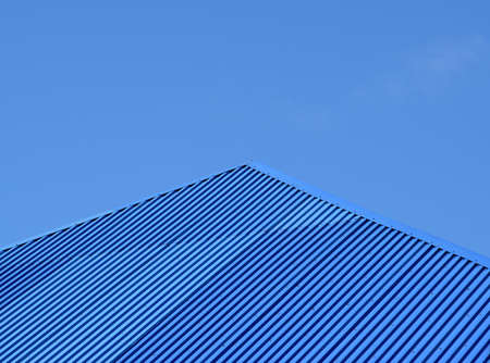 gable home renovation: Blue roof metal sheets. Modern types of roofing materials.