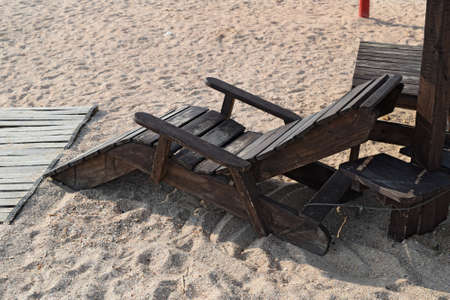 chaise lounge: Wooden chaise lounge on the beach. Furniture for a beach holiday.
