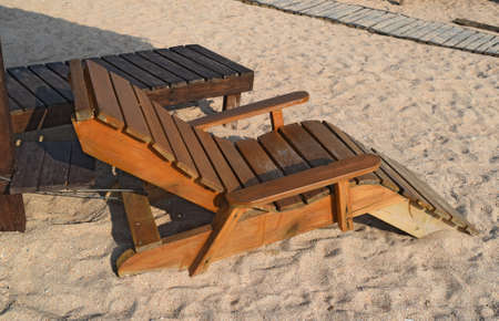 ionio: Wooden chaise lounge on the beach. Furniture for a beach holiday.