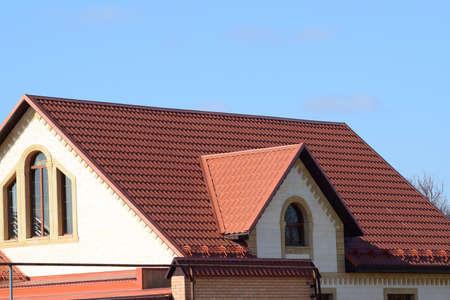 Una casa con un techo de chapas metálicas. La casa con aguilones, ventanas y techo de metal, equipado con rebosadero y la protección contra la nieve. Foto de archivo