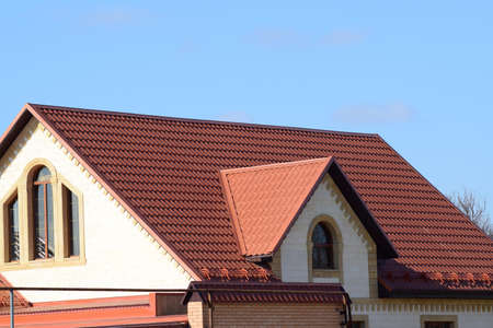 A house with a roof made of metal sheets. The house with gables, windows and metal roof, equipped with overflow and protection from snow.