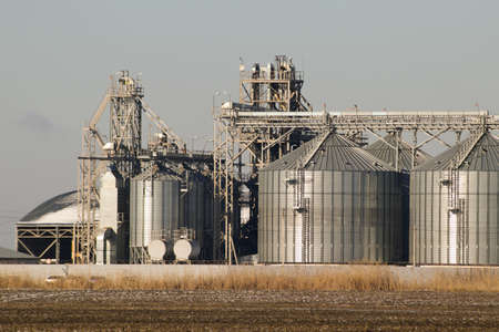 grain storage: Plant for the drying and storage of grain. Rice plant in the middle of fields. Stock Photo