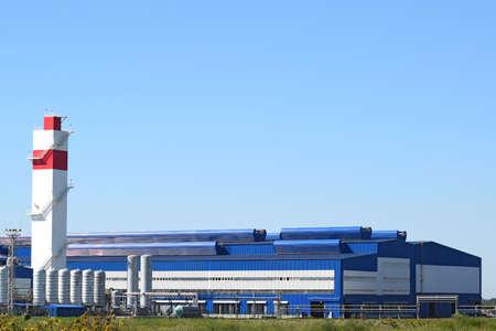 Große Anlage für die Verarbeitung von Schrott. Sehr große Fabrik alten Metall-Refiner. Blaues Dach des Fabrikgebäudes. Die Auspuffrohre, Heizkörper, Kühlindustrieanlagen sowie Bürogebäuden.
