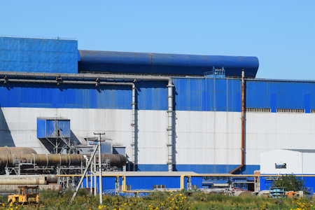 metallurgic: Big plant for processing scrap metal. Huge factory old metal refiner. Blue roof of the factory building. Exhaust pipes, radiators, cooling industrial units as well as office buildings. Stock Photo