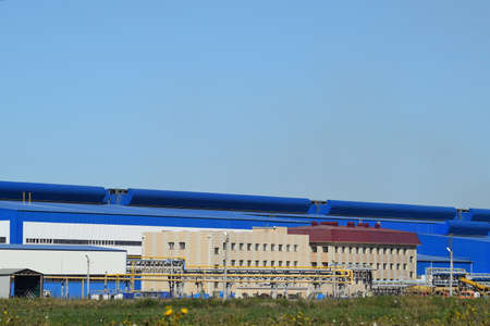smelting plant: Big plant for processing scrap metal. Huge factory old metal refiner. Blue roof of the factory building. Exhaust pipes, radiators, cooling industrial units as well as office buildings. Stock Photo