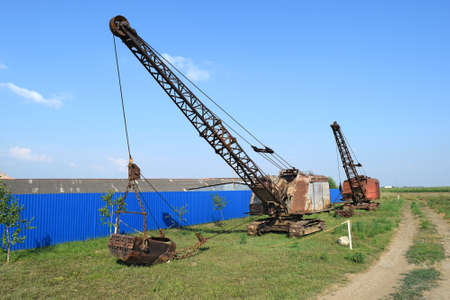 dragline: Old dragline near the blue fence. Old equipment for digging the soil in canals and quarries.