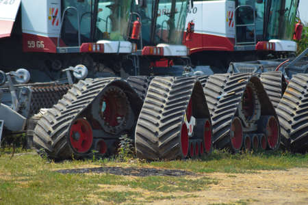 crawler: Russia, Temryuk - 19 July 2015: Rubber crawler tracks combine harvesters. Parking of agricultural machinery.