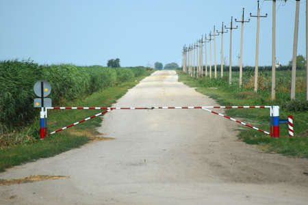 barrier: Road closed barrier. Dirt road among the agricultural fields. Closed Zone. Stock Photo