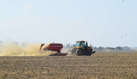 cultivator: Russia, Temryuk - 19 July 2015: Tractor rides on the field and makes the fertilizer into the soil. Clouds of dust from the dry soil tractor trailer. Fertilizers after plowing the field. Editorial