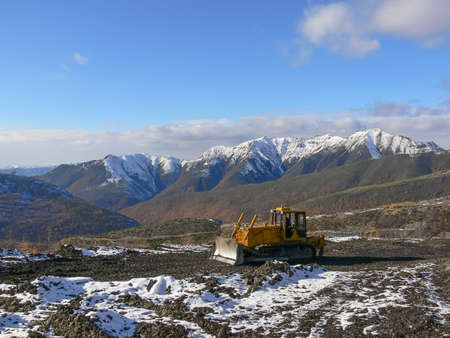 leveler: Crawler tractor with grederom against the backdrop of snow-capped mountains. Alignment grederom area for technological needs.
