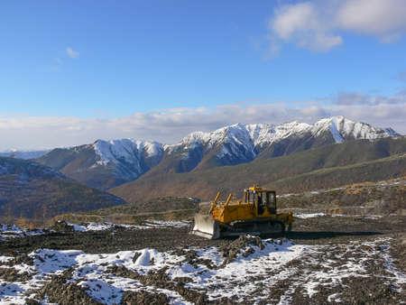 trattore cingolato con grederom sullo sfondo delle montagne innevate. zona grederom allineamento per esigenze tecnologiche.
