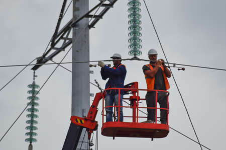 construction crew: Russia, village Poltavskaya - June 23, 2015: Power line support, insulators and wires. Appearance of a design. Assembly and installation of new support and wires of a power line.