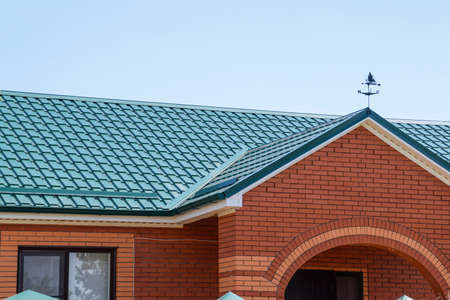 gable home renovation: Facade of a brick building with a green roof made of metal. Roof metal sheets. Modern types of roofing materials.
