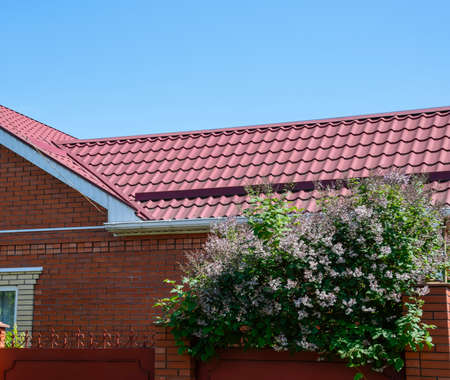 Facade of a brick building with a roof made of brown metal. Roof metal sheets. Modern types of roofing materials.