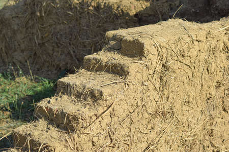 adobe: Old adobe wall closeup in sunny day. Sample construction of adobe walls. Stock Photo