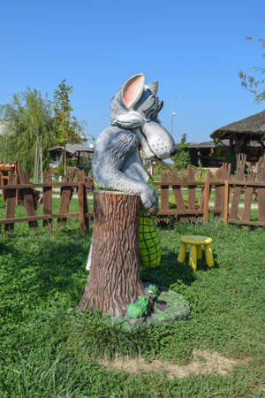 bipedal: Statue of fairy wolf. Wolf near a stump with frogs. Stock Photo