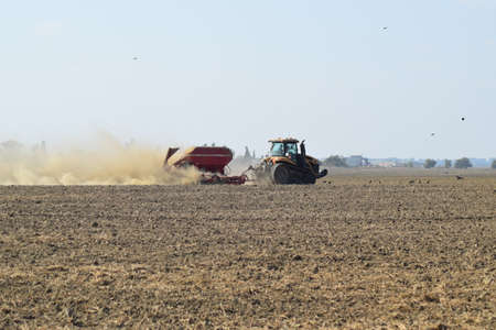 seed drill: Russia, Temryuk - 19 July 2015: Tractor rides on the field and makes the fertilizer into the soil. Clouds of dust from the dry soil tractor trailer. Fertilizers after plowing the field. Editorial