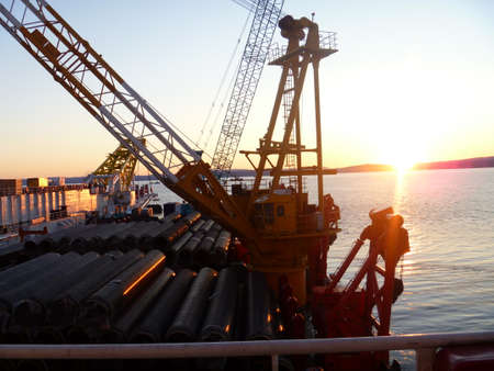 Deck pipe-laying vessel. pipes, valves and other equipment on the deck.