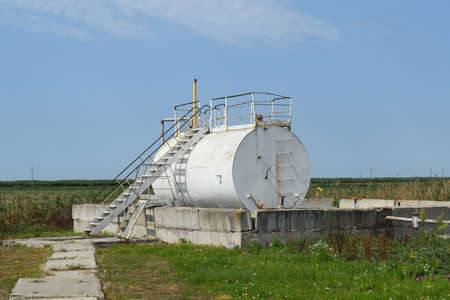 tightness: Barrel of oil separation. The equipment in the oil fields. Pipes, pumps and units. Stock Photo