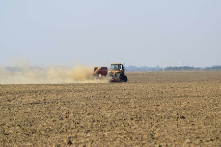 Russia, Temryuk - 19 July 2015: Tractor rides on the field and makes the fertilizer into the soil. Clouds of dust from the dry soil tractor trailer. Fertilizers after plowing the field. Editorial