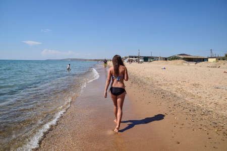 girl walking on the beach rear view walk the dark haired woman