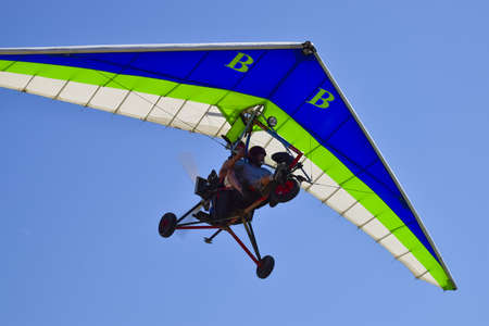 great danger: Russia, Veselovka - September 6, 2016: Trike, flying in the sky with two people. Extreme Entertainment travelers.