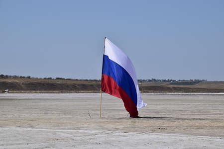 attributes: Russia, Veselovka - September 6, 2016: Russian flag on the bottom of a salty lake. Attributes country. Editorial