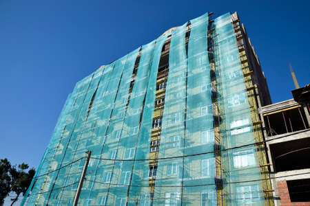 safety net: Safety net in the newly built high-rise building. Green grid on building of objects falling from a height.