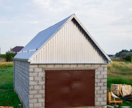 roof profile: Small garage with a roof of corrugated sheet metal. Garage with steel gates.