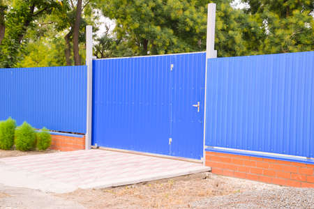 corrugation: Blue gate and fence. Fence of the private house with blue fence and a gate.